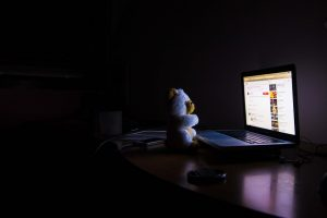 A teddy bear staring at a laptop