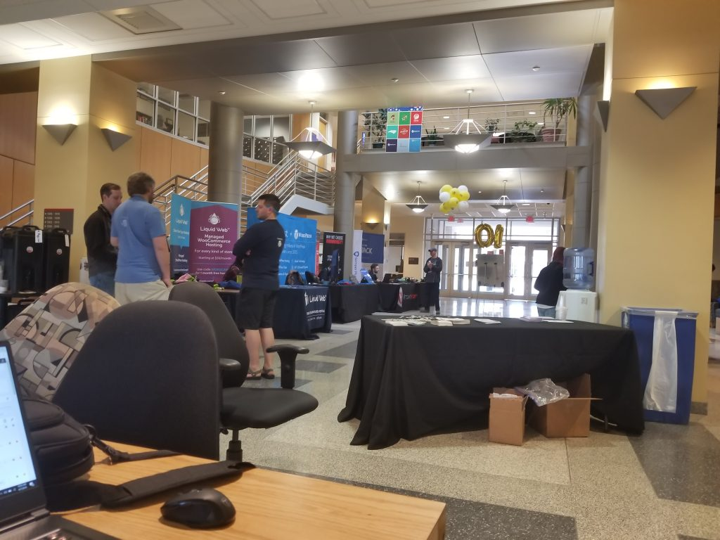 A picture of a few people standing around talking at wordcamp raleigh.