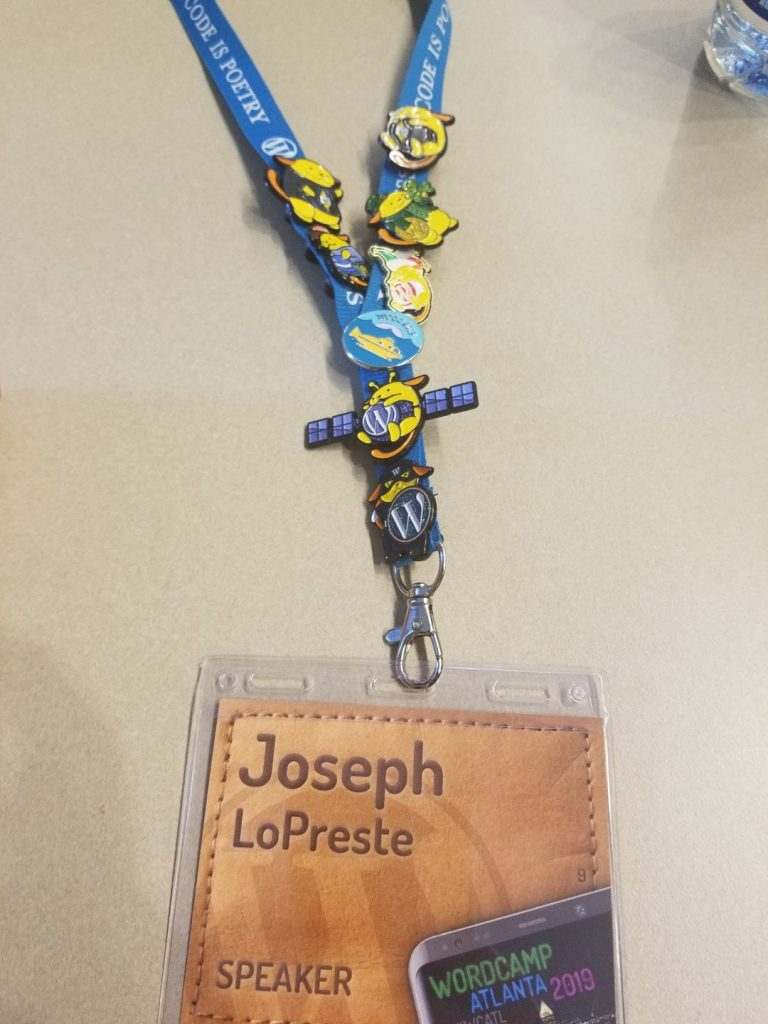 a lanard with wapuu pins on it and holding a speaker card with the name Joseph LoPreste on it